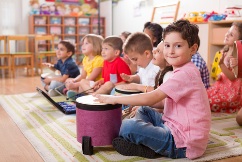 A group of pre-school boys and girls in a classroom.  They are p